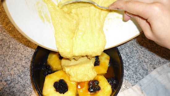 The upside-down cake mix being poured onto the fruit