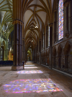 Coloured light lying on the stone floor Lincoln Cathedral's nave