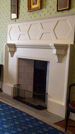 Off-white panelling above a Standen bedroom's fireplace